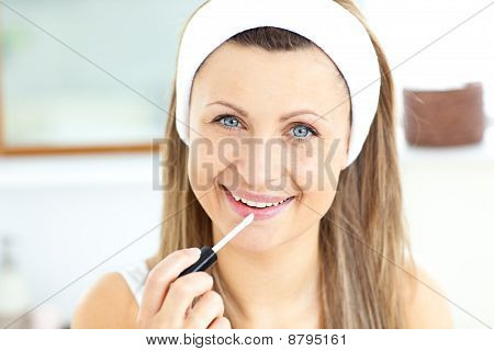 Portrait Of A Beautiful Woman Using Gloss Looking At The Camera