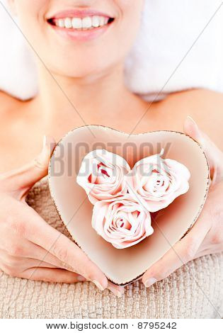 Close-up Of A Smiling Woman Holding A Bowl In The Shape Of A Heart With Flowers