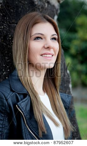 Cool pretty woman thinking at the park with a leather jacket