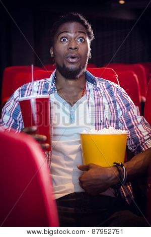 Happy young man watching a film at the cinema
