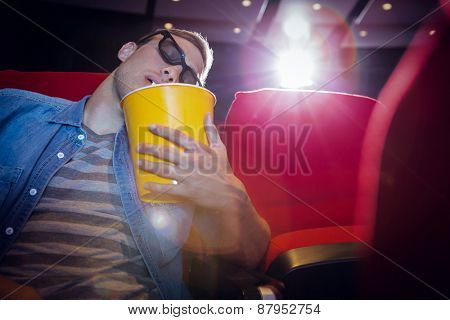 Young man sleeping in chair at the cinema