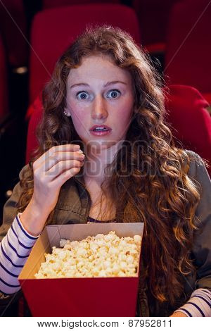 Surprised young woman watching a film at the cinema