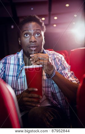 Young man watching a film and drinking soda at the cinema
