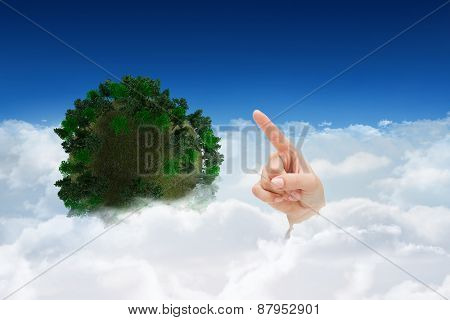 Hand pointing against bright blue sky over clouds