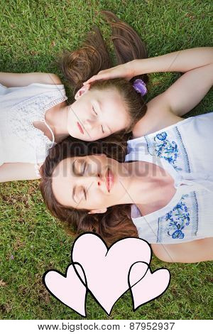 hearts against mother and daughter lying on grass