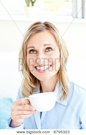 Bright Businesswoman Drinking Coffee Sitting On A Sofa At Home