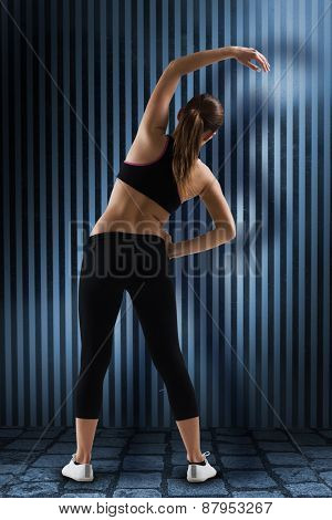 Fit brunette stretching rear view against dark grey room