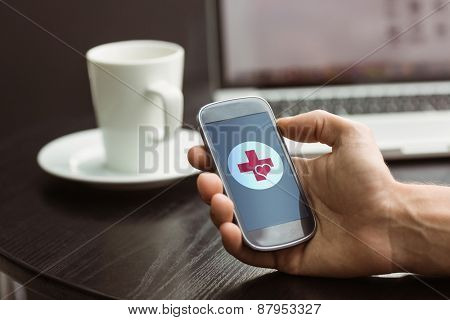 Hand holding smartphone against heart and cross
