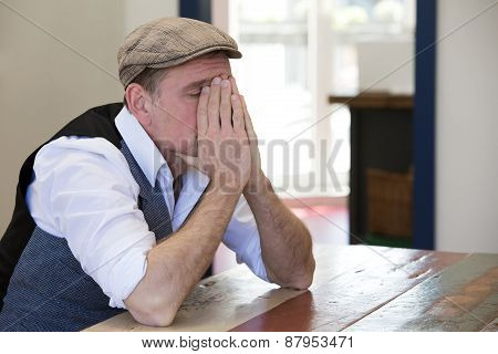 Man Sitting At Table Looking Tired