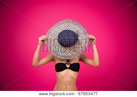 Woman in bikini covering her face with hat over pink background