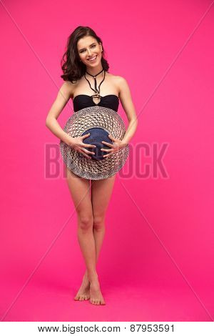 Full length portrait of a smiling woman in swimsuit posing with hat over pink background