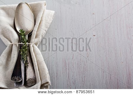 Vintage spoons and thyme on a napkin