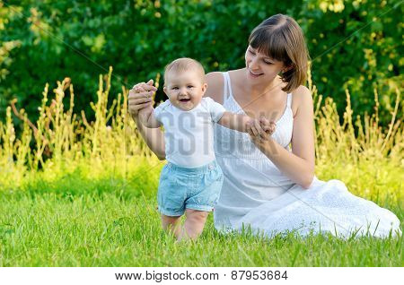 mother playing with adorable baby on green grass