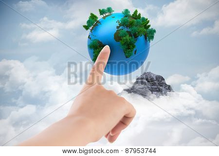Female hand pointing against mountain peak through the clouds