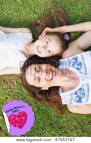 happy mothers day against mother and daughter lying on grass