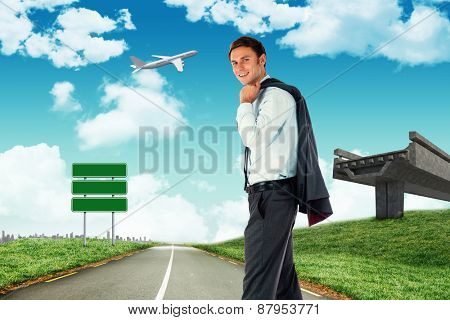 Smiling businessman holding his jacket against road leading out to the horizon