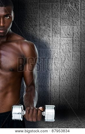 Serious fit shirtless young man lifting dumbbell against dark grey room