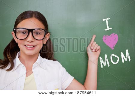 Cute pupil pointing against green chalkboard