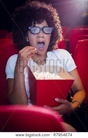 Surprised young woman watching a 3d film at the cinema