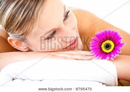 Close-up Of A Bright Woman Lying On A Massage Table With A Flower