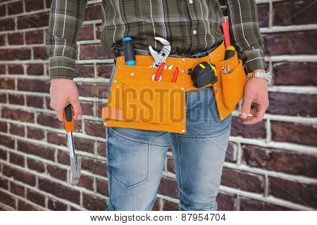 Manual worker holding hammer against red brick wall