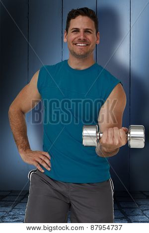 Portrait of a fit man exercising with dumbbell against dark grey room
