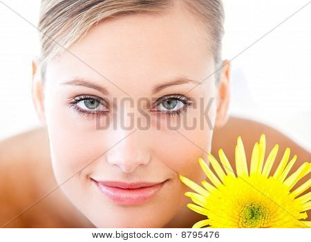 Close-up Of A Radiant Woman Lying On A Massage Table With A Flower