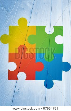 Autism awareness jigsaw against bleached wooden planks background