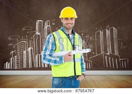 Portrait of smiling architect holding blueprint against room with wooden floor