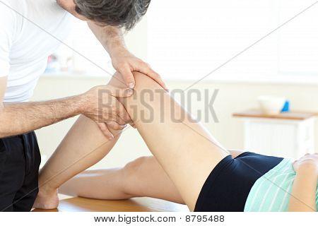 Guapo joven fisioterapeuta dando un masaje de piernas