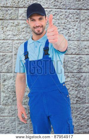 Repairman gesturing thumbs up against grey brick wall