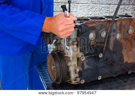 Male mechanic repairing car engine against grey brick wall