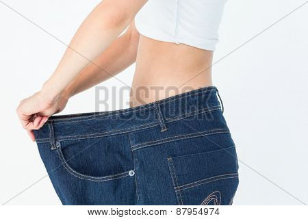 Woman belly in too big pants on white background