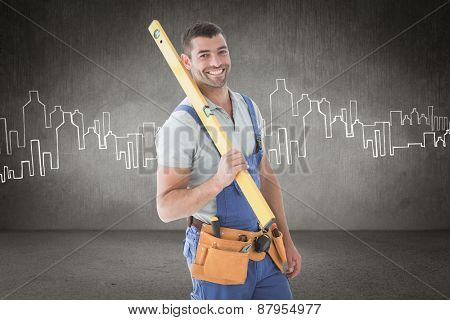 Worker holding spirit level against hand drawn city plan