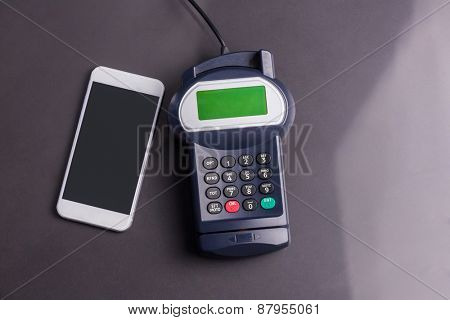 Overhead of pin terminal and smartphone against grey background