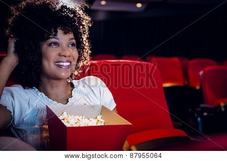 Smiling young woman watching a film at the cinema