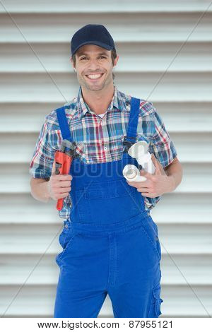 Plumber holding monkey wrench and sink pipe against grey shutters