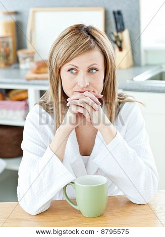 Thoughtful Woman Holding A Cup Of Coffee In The Kitchen