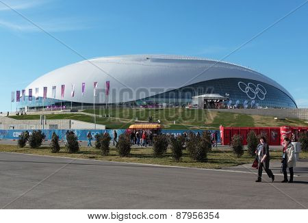 SOCHI, RUSSIA - FEBRUARY 12, 2014: People walking against the Bolshoy Ice Dome in the Olympic Park. This sport venue hosted ice hockey competitions of the 2014 Winter Olympics