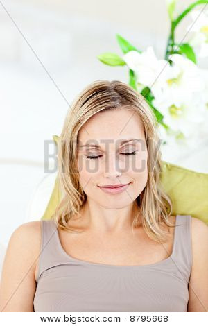 Relaxed Young Woman With Closed Eyes Lying On A Sofa