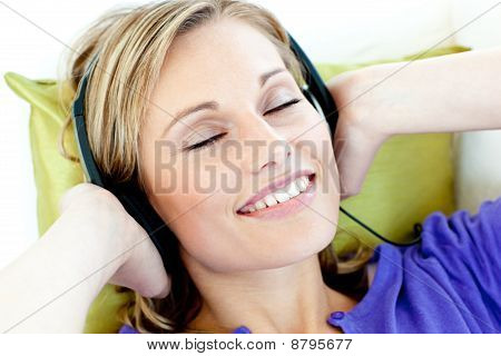 Charming Caucasian Woman Listening To Music With Headphones Lying On A Sofa