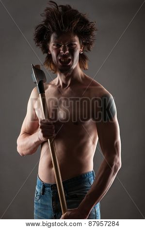 aggressive dirty man with an ax in hands