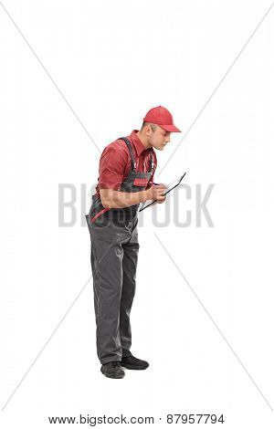 Full length portrait of a mechanic in a gray jumpsuit writing down notes on a clipboard isolated on white background