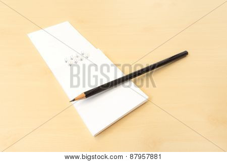White Memo Note With Black Sharp Pencil On Wooden Surface