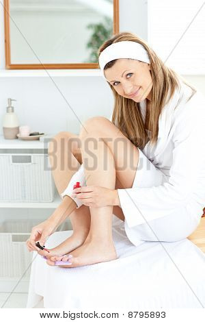 Happy Caucasian Woman Varnishing Her Toenails In The Bathroom