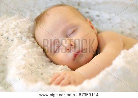 Sleeping Newborn Baby Girl In White Blankets