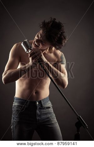 emotional singer singing into retro microphone