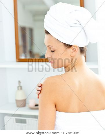 Pleased Young Woman With A Towel Putting Cream On Her Face In The Bathroom