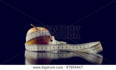 Fresh Apple Wrapped With A White Measuring Tape