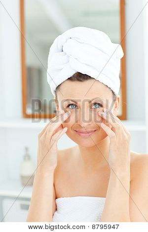 Beautiful Young Woman With A Towel Putting Cream On Her Face In The Bathroom